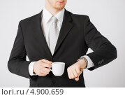 Бизнесмен в черном пиджаке смотрит на часы. Стоковое фото, фотограф Syda Productions / Фотобанк Лори