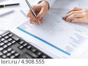 Купить «Молодая женщина работает за столом с деловыми бумагами», фото № 4908555, снято 24 апреля 2013 г. (c) Syda Productions / Фотобанк Лори