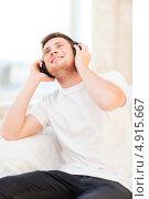 Купить «Молодой меломан с наушниками наслаждается музыкой», фото № 4915667, снято 6 июня 2013 г. (c) Syda Productions / Фотобанк Лори