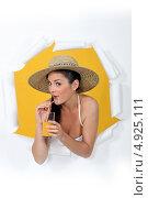 Купить «Девушка в шляпе пьет сок через трубочку, выглядывая из дыры в бумаге», фото № 4925111, снято 23 декабря 2010 г. (c) Phovoir Images / Фотобанк Лори