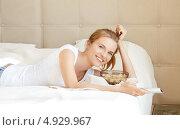 Счастливая девушка лежит на кровати и улыбается. Стоковое фото, фотограф Syda Productions / Фотобанк Лори