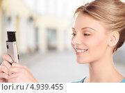 Купить «Молодая женщина фотографирует на телефон на городской улице», фото № 4939455, снято 12 декабря 2009 г. (c) Syda Productions / Фотобанк Лори
