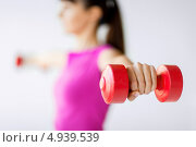 Купить «Спортивная девушка тренируется с легкими гантелями», фото № 4939539, снято 15 мая 2013 г. (c) Syda Productions / Фотобанк Лори