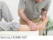 Купить «Мануальный терапевт держит ногу девушки», фото № 4948167, снято 21 марта 2012 г. (c) Wavebreak Media / Фотобанк Лори