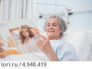 Купить «Женщина с улыбкой читает глянцевый журнал в больничной койке», фото № 4948419, снято 25 апреля 2012 г. (c) Wavebreak Media / Фотобанк Лори