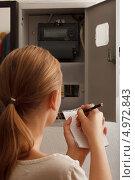 Купить «Молодая женщина переписывает показания электрического счетчика», фото № 4972843, снято 12 июля 2013 г. (c) Данил Руденко / Фотобанк Лори