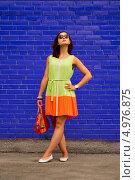 Девушка в легком ярком платье стоит на фоне синей стены. Стоковое фото, фотограф Юрий Селиванов / Фотобанк Лори
