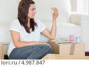 Купить «Молодая брюнетка держит в руках желтый колер, сидя на ковре среди картонных коробок», фото № 4987847, снято 4 июля 2012 г. (c) Wavebreak Media / Фотобанк Лори