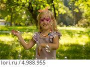 Девочка с декоративным макияжем ловит мыльные пузыри в парке. Стоковое фото, фотограф Tanya Lomakivska / Фотобанк Лори