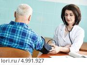 Купить «Доктор меряет давление пожилому мужчине», фото № 4991927, снято 12 марта 2013 г. (c) Дмитрий Калиновский / Фотобанк Лори