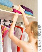Женщина выбирает одежду в   гардеробе. Стоковое фото, фотограф Евгений Атаманенко / Фотобанк Лори