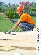 Купить «Плотник забивает гвоздь в деревянный брус на крыше», фото № 4997751, снято 23 августа 2013 г. (c) Дмитрий Калиновский / Фотобанк Лори