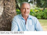 Купить «мужчина сидит около ствола старого дерева в саду и улыбается», фото № 5009951, снято 5 апреля 2013 г. (c) Wavebreak Media / Фотобанк Лори