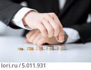 Купить «Бизнесмен сидит за столом и раскладывает монеты по стопкам», фото № 5011931, снято 22 марта 2013 г. (c) Syda Productions / Фотобанк Лори