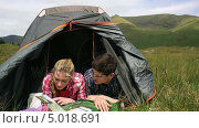 Купить «Couple reading map lying in their tent», видеоролик № 5018691, снято 20 июля 2019 г. (c) Wavebreak Media / Фотобанк Лори