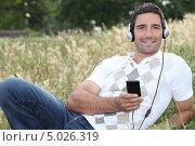 Мужчина слушает музыку в плеере на природе. Стоковое фото, фотограф Phovoir Images / Фотобанк Лори