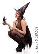 Девушка в костюме ведьмы с  фигуркой волшебника на ладони. Стоковое фото, фотограф Наталья Алексахина / Фотобанк Лори
