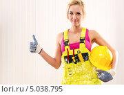 """Купить «Девушка в рабочем комбинезоне с каской в руке показывает жест """"все отлично""""», фото № 5038795, снято 16 апреля 2013 г. (c) Alexander Tihonovs / Фотобанк Лори"""
