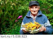 Купить «Пожилой мужчина в саду держит гроздья спелой облепихи», эксклюзивное фото № 5038923, снято 9 сентября 2013 г. (c) Яна Королёва / Фотобанк Лори