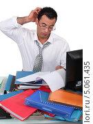 Купить «Мужчина чешет голову, сидя за столом, заваленным папками с документами», фото № 5061435, снято 10 марта 2011 г. (c) Phovoir Images / Фотобанк Лори