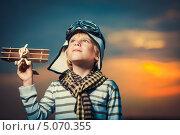 Купить «Мальчик в шлеме пилота стоит с деревянным самолетом в руке на фоне закатного неба», фото № 5070355, снято 13 июля 2013 г. (c) Raev Denis / Фотобанк Лори