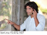 Симпатичный брюнет говорит по телефону возле карты на стене. Стоковое фото, фотограф Phovoir Images / Фотобанк Лори