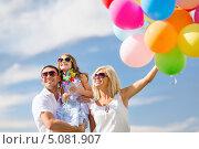 Счастливая семья с дочкой с разноцветными воздушными шарами летним солнечным днем. Стоковое фото, фотограф Syda Productions / Фотобанк Лори