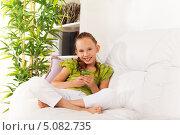 Купить «Улыбающаяся девочка сидит на диване с мобильным телефоном», фото № 5082735, снято 4 августа 2013 г. (c) Сергей Новиков / Фотобанк Лори