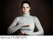 Купить «Поясной портрет красивой женщины в водолазке, которая что-то защищает руками», фото № 5087671, снято 27 октября 2012 г. (c) Николай Винокуров / Фотобанк Лори