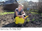 Улыбающаяся женщина с лейкой на дачном участке, фото № 5102927, снято 12 мая 2013 г. (c) Евгений Ткачёв / Фотобанк Лори