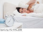 Купить «Брюнетка затыкает уши подушками», фото № 5115239, снято 28 августа 2012 г. (c) Wavebreak Media / Фотобанк Лори