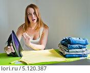 Купить «Молодая женщина с горячим утюгом в гладильной комнате», фото № 5120387, снято 14 августа 2013 г. (c) Валерия Потапова / Фотобанк Лори