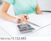 Купить «Девушка сидит за столом и считает что-то на калькуляторе», фото № 5132883, снято 1 июня 2013 г. (c) Syda Productions / Фотобанк Лори