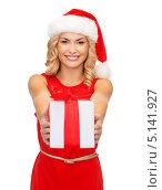 Купить «Счастливая девушка с локонами в шапке Санты с новогодним подарком», фото № 5141927, снято 27 сентября 2013 г. (c) Syda Productions / Фотобанк Лори