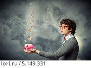 Купить «бизнесмен с копилкой на фоне туч», фото № 5149331, снято 26 мая 2020 г. (c) Sergey Nivens / Фотобанк Лори