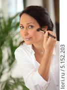 Купить «Женщина с улыбкой наносит макияж кисточкой», фото № 5152203, снято 28 февраля 2010 г. (c) Phovoir Images / Фотобанк Лори