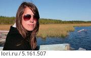 Купить «Девушка в солнечных очках сидит на берегу озера», видеоролик № 5161507, снято 11 октября 2013 г. (c) Кекяляйнен Андрей / Фотобанк Лори