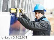 Купить «Строитель в синей строительной каске стоит с уровнем около стены», фото № 5162671, снято 11 октября 2013 г. (c) Дмитрий Калиновский / Фотобанк Лори