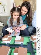 Купить «Мама и дочка рассматривают макет своего нового дома», фото № 5172067, снято 21 января 2010 г. (c) Phovoir Images / Фотобанк Лори