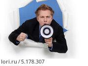 Купить «Человек в костюме кричит в мегафон, высунувшись в дыру в бумаге», фото № 5178307, снято 14 января 2011 г. (c) Phovoir Images / Фотобанк Лори