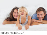 Купить «Счастливая семья выглядывает из-под одеяла», фото № 5184707, снято 12 октября 2012 г. (c) Wavebreak Media / Фотобанк Лори