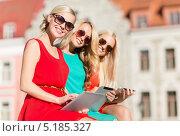Купить «Счастливые девушки в ярких платьях на улице летним днем с планшетным компьютером», фото № 5185327, снято 8 сентября 2013 г. (c) Syda Productions / Фотобанк Лори