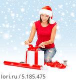 Купить «Красивая девушка в красной шапке Санта-Клауса завязывает бант на коробке с подарком», фото № 5185475, снято 15 августа 2013 г. (c) Syda Productions / Фотобанк Лори