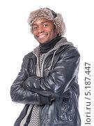 Улыбающийся мужчина в зимней одежде стоит, сложив руки на груди. Изолировано на белом. Стоковое фото, фотограф Discovod / Фотобанк Лори