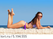 Купить «Девушка в бикини лежит на каменной стене на фоне моря», фото № 5194555, снято 26 августа 2012 г. (c) Сергей Сухоруков / Фотобанк Лори