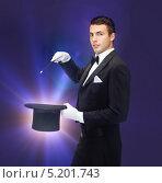 Купить «Молодой человек во фраке показывает фокусы», фото № 5201743, снято 12 сентября 2013 г. (c) Syda Productions / Фотобанк Лори