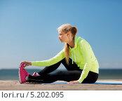 Спортивная девушка делает зарядку на свежем воздухе. Стоковое фото, фотограф Syda Productions / Фотобанк Лори