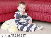 Годовалый малыш грызет ногти, сидя на полу у дивана. Стоковое фото, фотограф ivolodina / Фотобанк Лори
