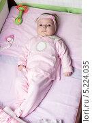 Купить «Малышка в розовой одежде лежит в розовой кроватке», фото № 5224035, снято 18 апреля 2011 г. (c) Кекяляйнен Андрей / Фотобанк Лори