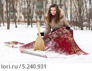 Купить «Девушка чистит коврик  на снегу», фото № 5240931, снято 5 декабря 2012 г. (c) Яков Филимонов / Фотобанк Лори